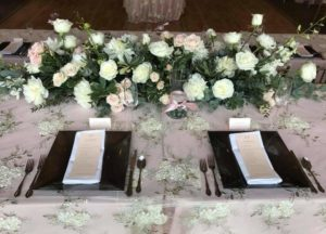 ivory mesh overlay with pewter charger plates and floral garland